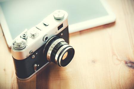 木製のテーブル上でタブレットを持つ古いビンテージ カメラ。