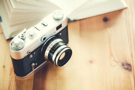 Old vintage camera with book on a wooden table. photo