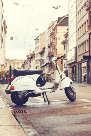 Vintage scooter parked at European street photo