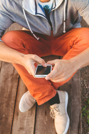 Young  hipster man using smart phone sitting on wooden boards