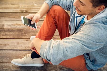 Jonge hipster man met behulp van slimme telefoon zit op houten planken Stockfoto