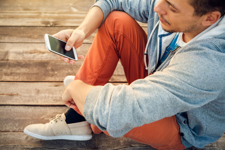 texting: Young  hipster man using smart phone sitting on wooden boards