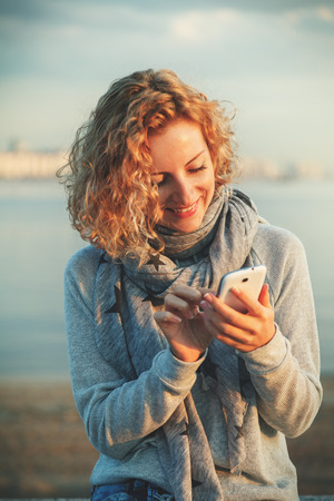 Beautiful young  hipster woman using smart phone at beach photo