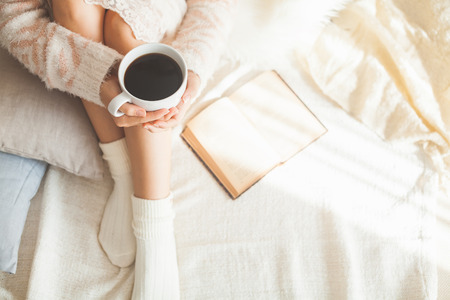 comfortable cozy: Soft photo of woman on the bed with old book and cup of coffee in hands, top view point