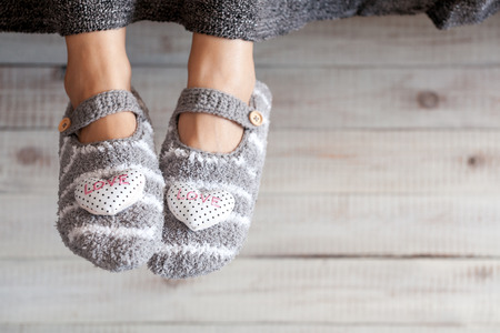 cold woman: Soft photo of woman feet in cute slippers, top view point