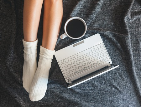 Soft photo of woman on the bed with notebook and cup of coffee, top view point photo