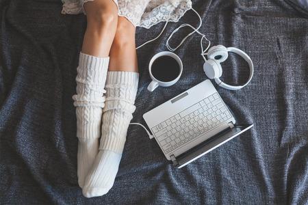 Foto suave de la mujer en la cama con el portátil, los auriculares y una taza de café, Punto de vista superior Foto de archivo