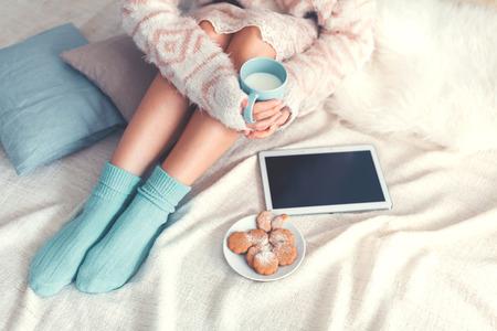 Zachte foto van de vrouw op het bed met tablet en kopje melk in handen, bovenaanzicht punt