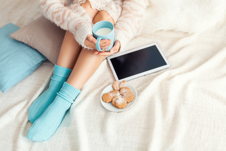 legwarmers: Soft photo of woman on the bed with tablet and cup of milk in hands, top view point