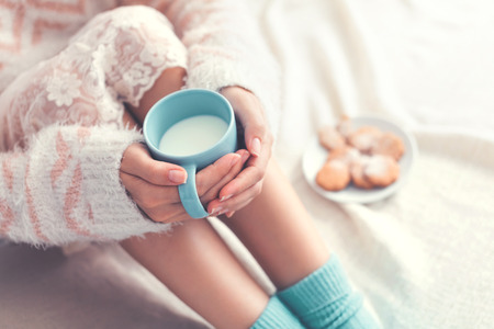 comfortable: Soft photo of woman on the bed with cup of milk in hands, top view point