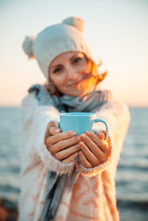 Cute young european woman in knitted clothes drinks coffee on the beach at sunset photo