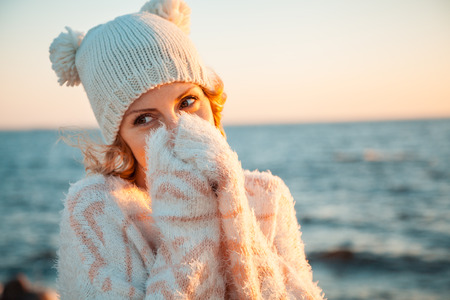 Cute young european woman in knitted clothes on the beach at sunset Stock Photo