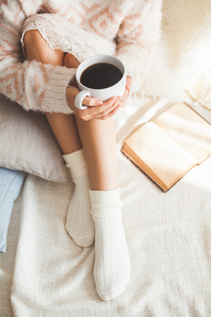 hand woven: Soft photo of woman on the bed with old book and cup of coffee in hands, top view point
