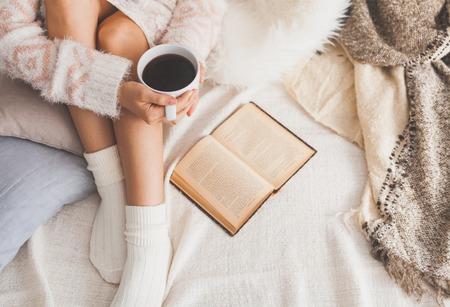 Zachte foto van de vrouw op het bed met oude boek en een kopje koffie in handen, bovenaanzicht punt