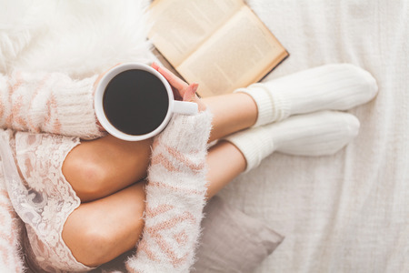 Soft photo of woman on the bed with old book and cup of coffee in hands, top view point