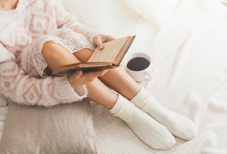 calcetines: Foto suave de la mujer en la cama con el libro viejo y una taza de café, Punto de vista superior Foto de archivo