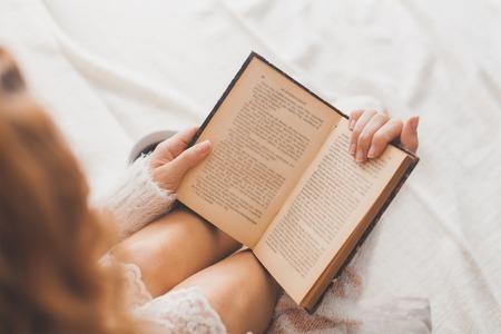 Eski kitap ve kahve fincan, üst bakış açısı ile yatakta kadın Yumuşak fotoğraf