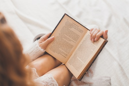 books: Soft photo of woman on the bed with old book and cup of coffee, top view point Stock Photo