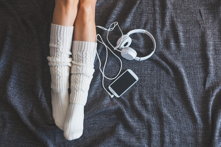 스마트 폰 및 헤드폰, 상위 뷰 포인트와 침대에 여자의 소프트 사진 스톡 콘텐츠