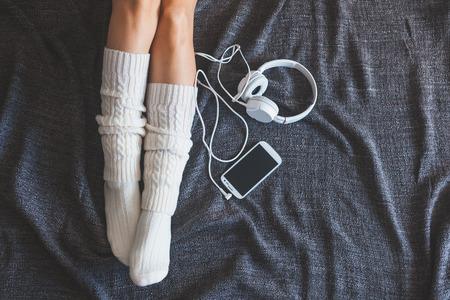 Foto suave de la mujer en la cama con el teléfono inteligente y auriculares, Punto de vista superior Foto de archivo