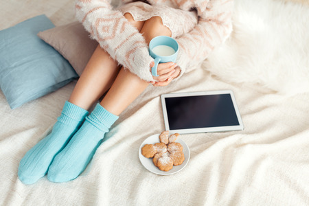 Soft photo of woman on the bed with tablet and cup of milk in hands, top view point photo