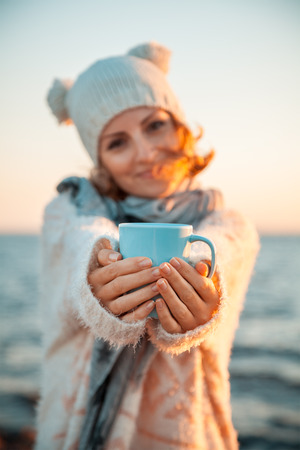 Cute young european woman in knitted clothes drinks coffee on the beach at sunset