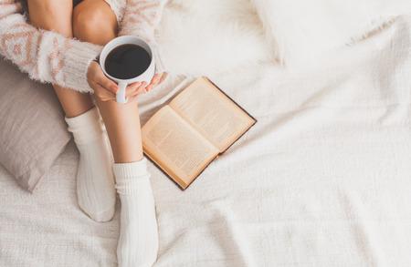 Soft-Foto der Frau auf dem Bett mit alten Buch und eine Tasse Kaffee in der Hand, Ansicht von oben Punkt