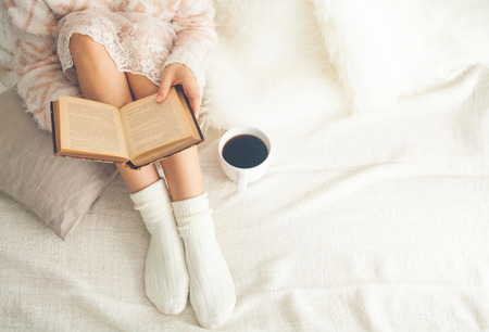 comfortable: Soft photo of woman on the bed with old book and cup of coffee, top view point Stock Photo