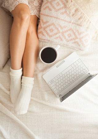 woman lying in bed: Soft photo of woman on the bed with notebook and cup of coffee, top view point