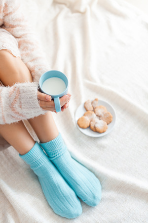 legwarmers: Soft photo of woman on the bed with cup of milk in hands, top view point
