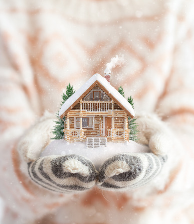 Young woman in mittens holding snow in her hands with a log house. Unusual christmas concept photo