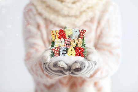 Young woman in mittens holding snow in her hands with colorful text Happy new year. Unusual christmas concept photo
