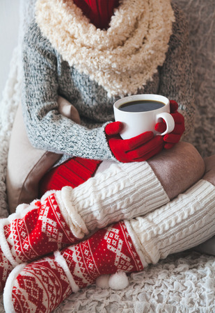 legwarmers: Woman sitting on the chair in light room with cup of coffee in hands in christmas, Stock Photo