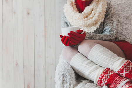 クリスマス、手でコーヒーを 1 杯で明るい部屋で椅子に座っている女性 写真素材