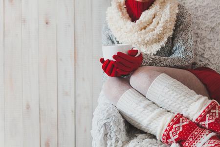 freddo: Donna seduta sulla sedia in stanza luce con una tazza di caff� in mano a Natale,
