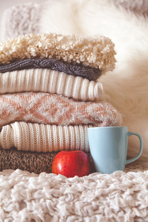 warm home: Stack of cozy knitted clothes with red apple and cup of tea