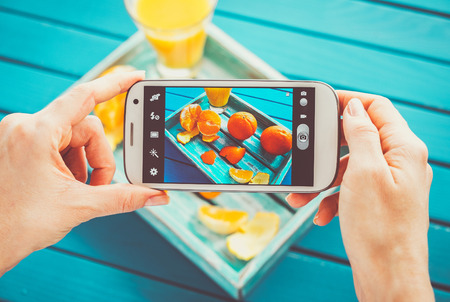 old picture: Woman taking picture of vintage tray with fruits on her smartphone. Top view