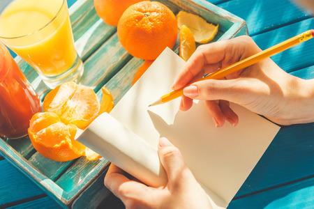 De vrouw schrijft in haar notebook in de zonnige ochtend. Stockfoto