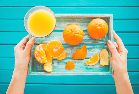 Woman holds a vintage tray with mandarins and fresh juice in her hands. Top view