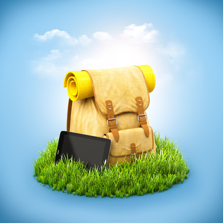 camp: Backpack with tablet on grass at blue background. Unusual travel background
