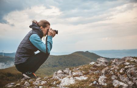 女性のカメラマンは山の風景を写真に撮る 写真素材