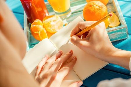 Frau steht in ihrem Notizbuch im sonnigen Morgen zu schreiben.
