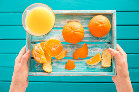 orange juice: Woman holds a vintage tray with mandarins and fresh juice in her hands. Top view