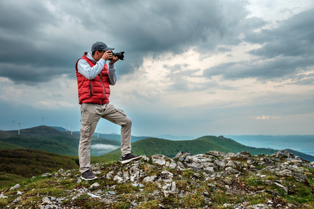 Photographer is taking a picture of  landscape in mountains Zdjęcie Seryjne
