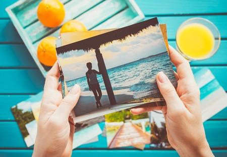 Vrouw op zoek naar foto's in haar handen. Bovenaanzicht.