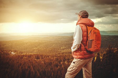 Man with backpack is standing on a mountain.