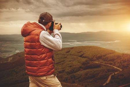 aventura: El fotógrafo es tomar una foto de la puesta de sol en las montañas Foto de archivo