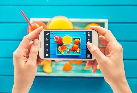 vrouw nemen foto van vintage dienblad met fruit op haar smartphone. Bovenaanzicht