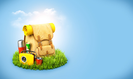 backpack: Backpack with termos, map and radio on grass at blue background. Unusual travel background Stock Photo