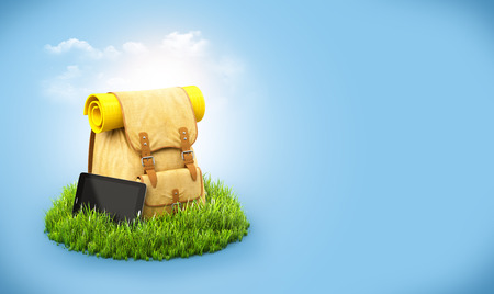 travel background: Backpack with tablet on grass at blue background. Unusual travel background